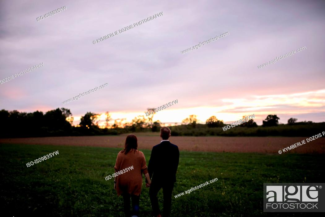 Stock Photo: Rear view of romantic couple in field watching sunset.