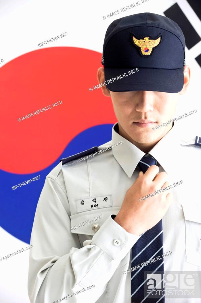 Stock Photo: police officer in front of Korean flag, Taegeukgi.