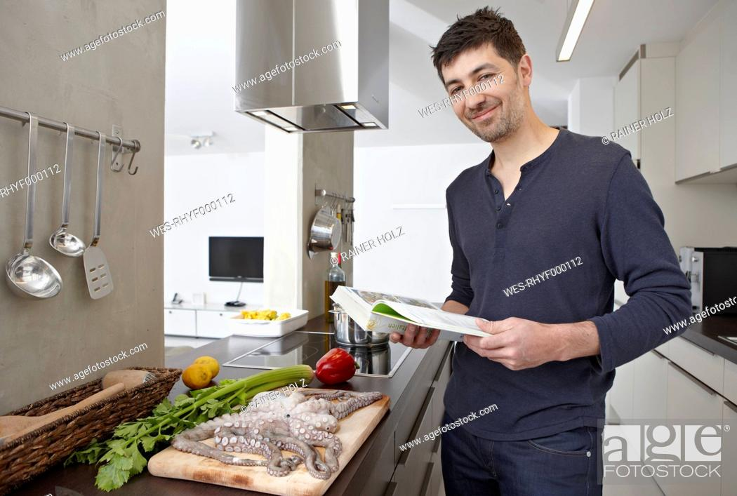 Stock Photo: Germany, Cologne, Mid adult man with cook book in kitchen, portrait.