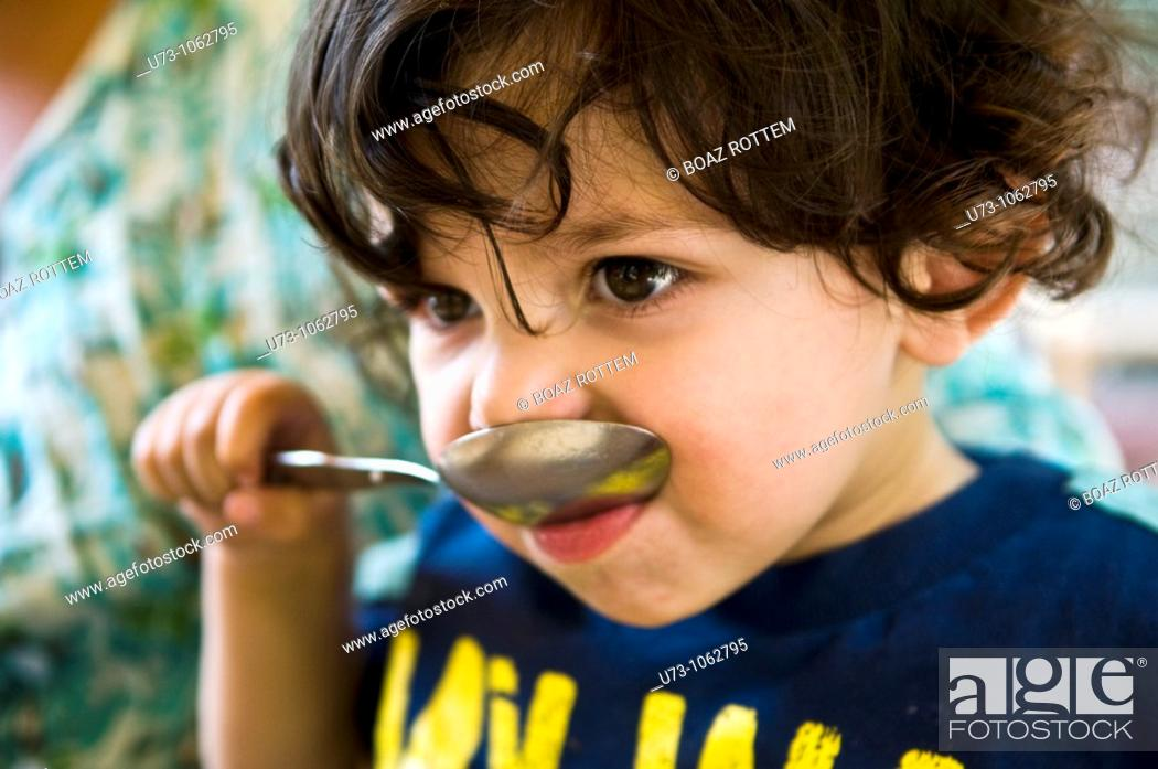 Stock Photo: A boy trying to eat with a big spoon.