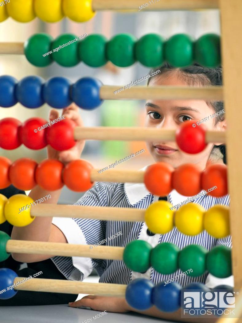 Stock Photo: Elementary schoolgirl looking through abacus sitting in classroom.