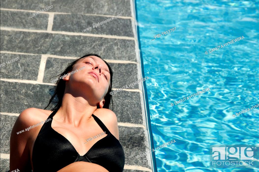 Stock Photo: young woman relaxing at swimming pool, summertime.