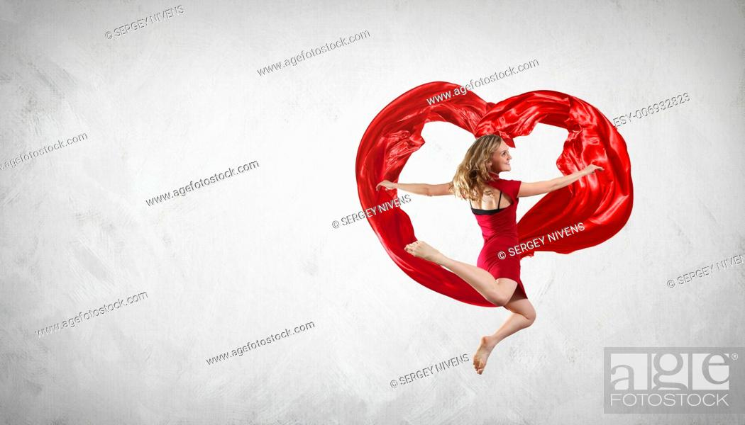 Stock Photo: Young woman dancing with red fabric in studio and heart symbol.