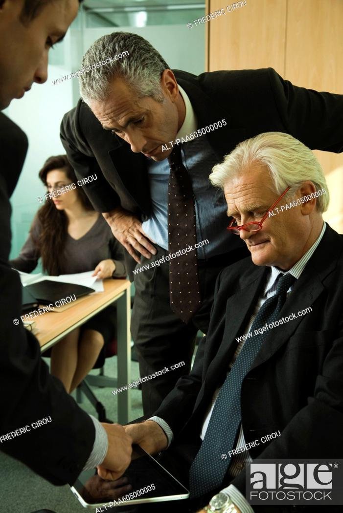 Stock Photo: Young businessman explaining to mature executives how to use digital tablet.