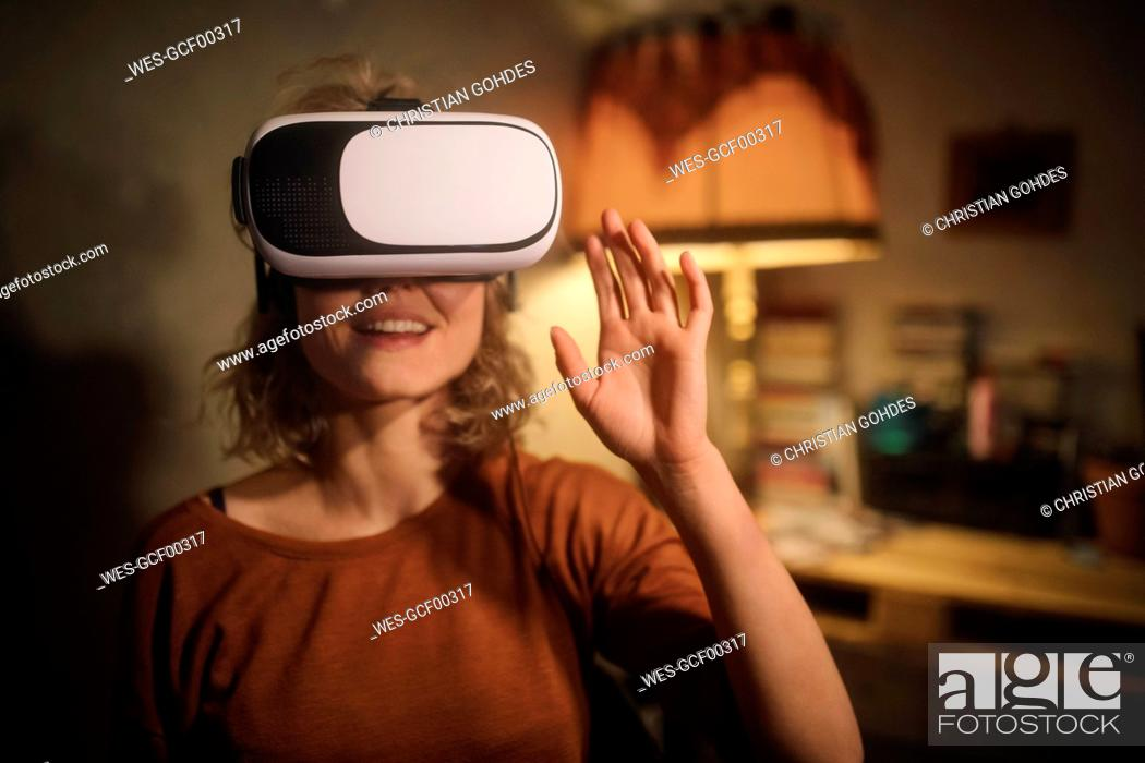 Stock Photo: Young woman using Virtual Reality Glasses at home.