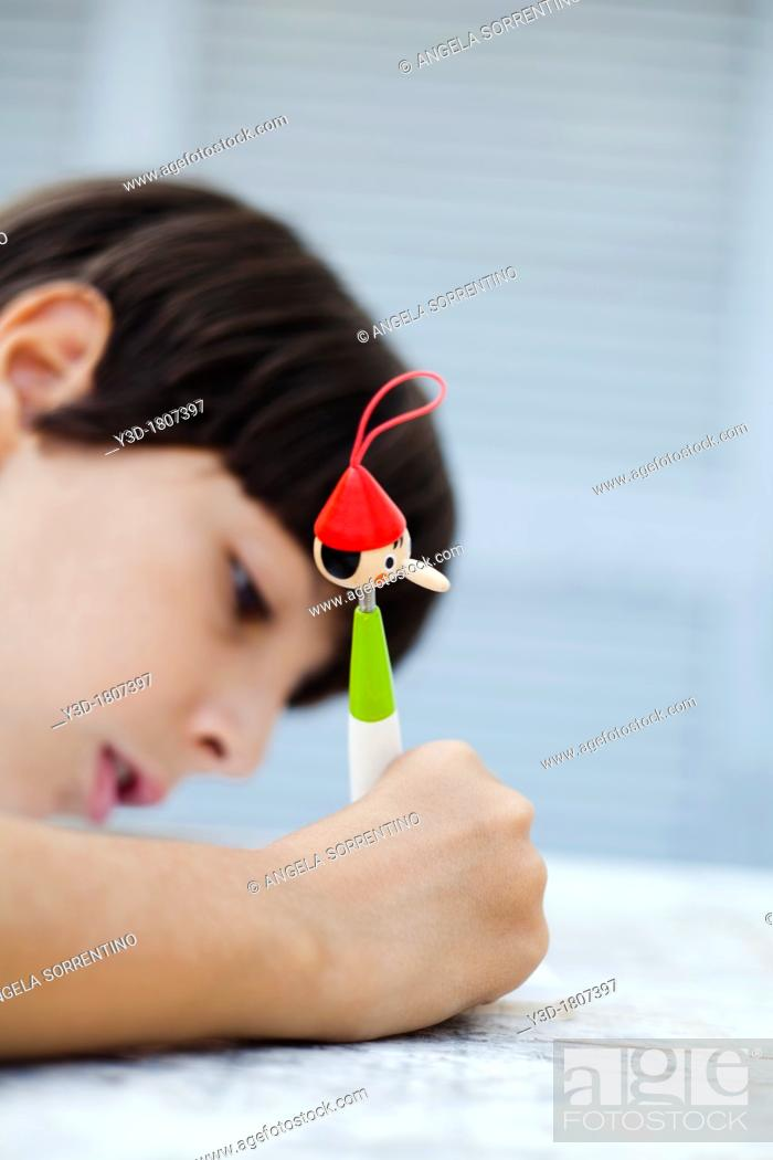 Imagen: Child Writing with Pinocchio shape pen, focus on the pen.