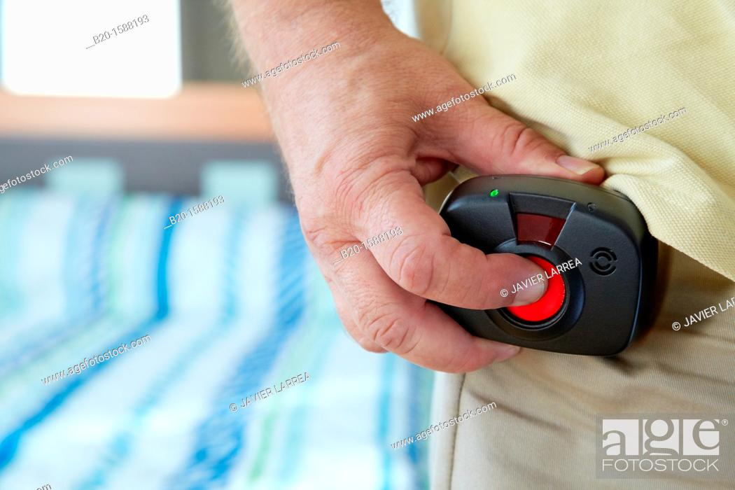 Stock Photo: Older person's hand holding the device with a mobile tele care for automatic detection of falls that sits at the waist  In the event of a fall tele care center.