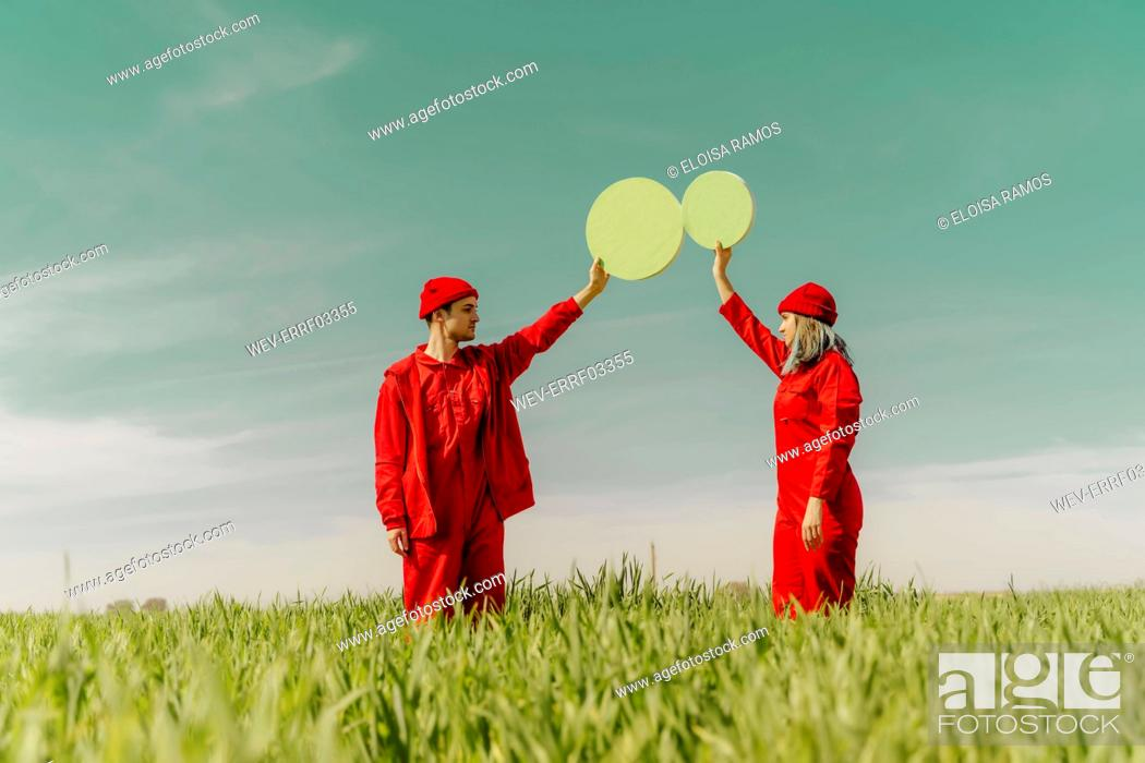 Stock Photo: Young couple wearing red overalls standing on a field holding two green circles.