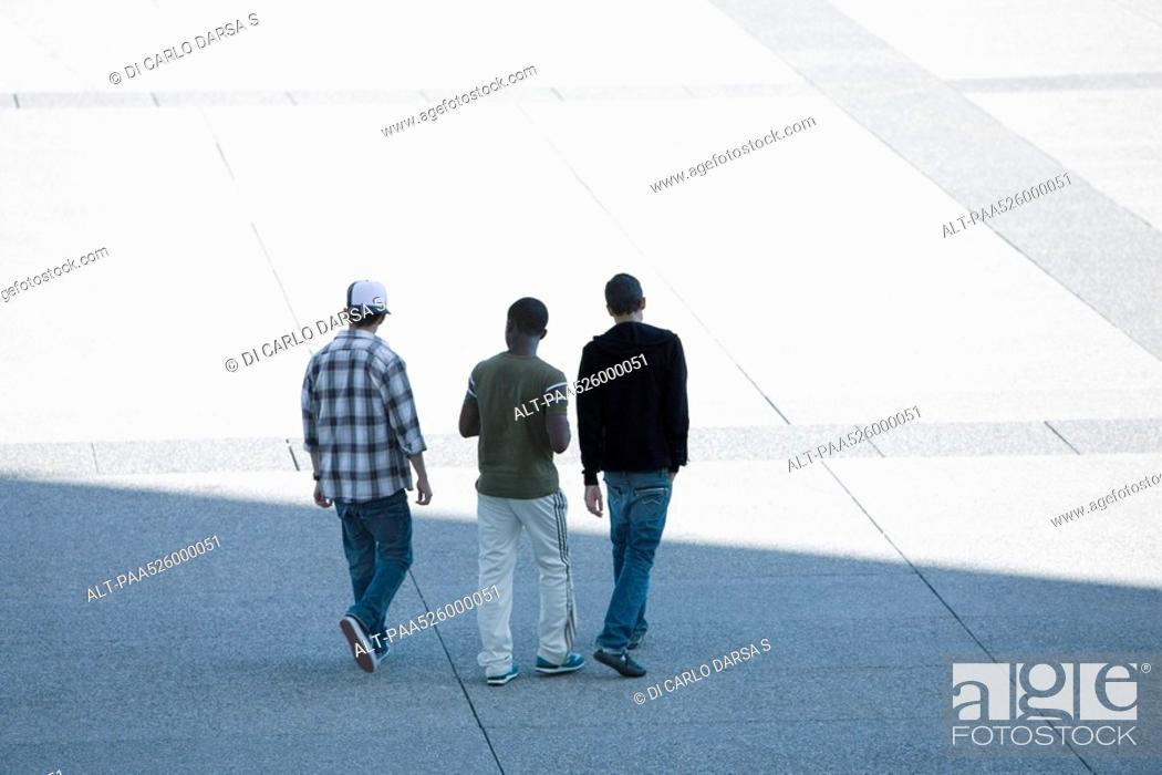 Stock Photo: Three young men walking together across public square.