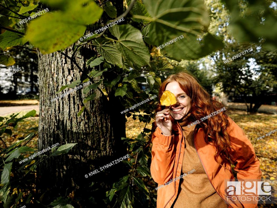 Stock Photo: Portrait of happy redheaded woman holding autumn leaf.