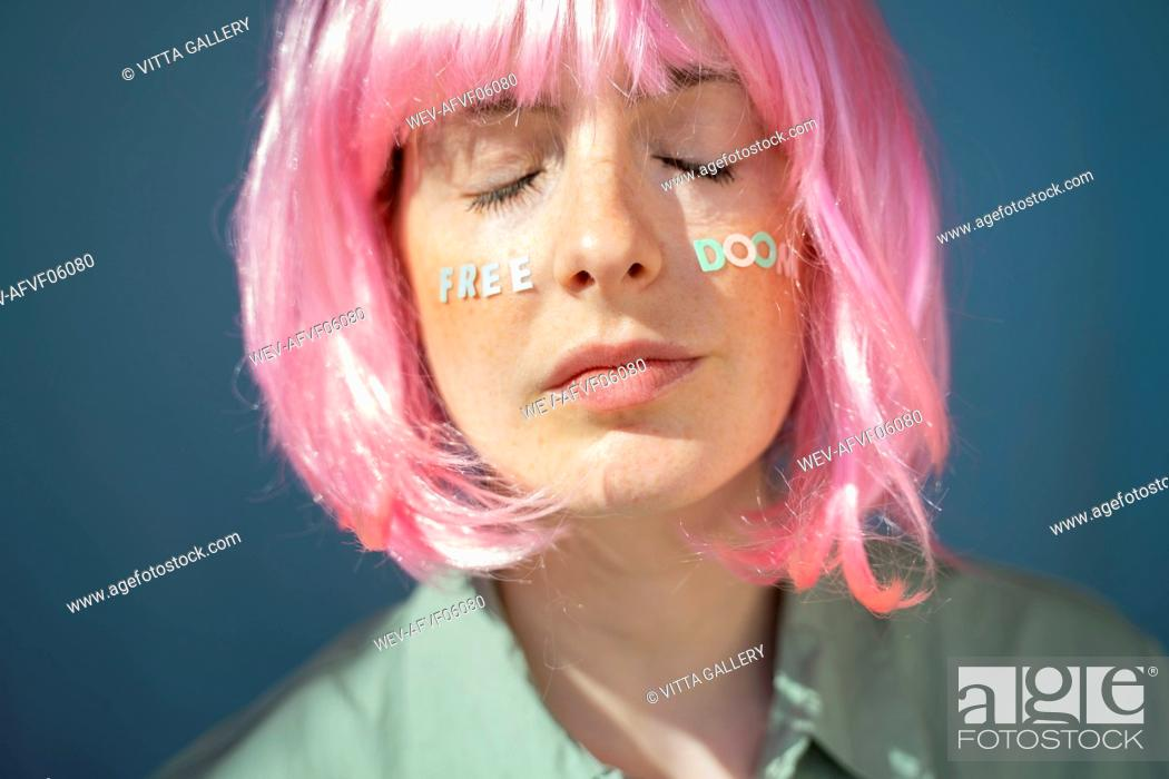 Stock Photo: Young woman wearing pink wig, letters on her face, free doom, with eyes closed.