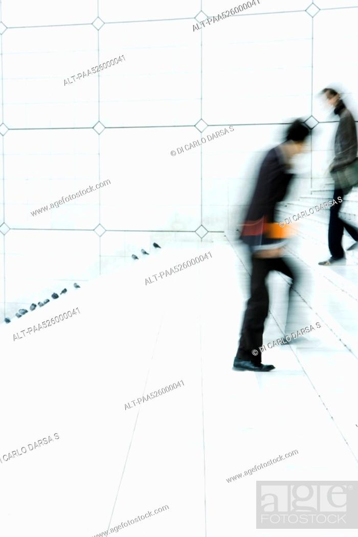 Stock Photo: Business people passing one another going up and down steps outdoors.