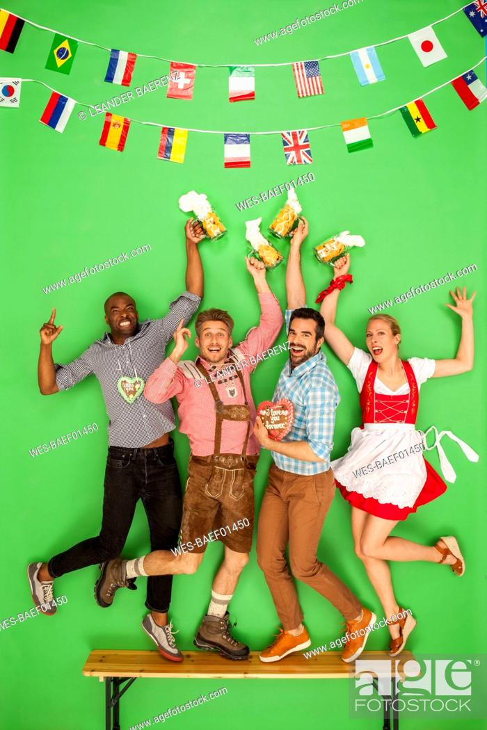 Stock Photo: Group of people at the Oktoberfest dancing on beer benchesm drinking beer.