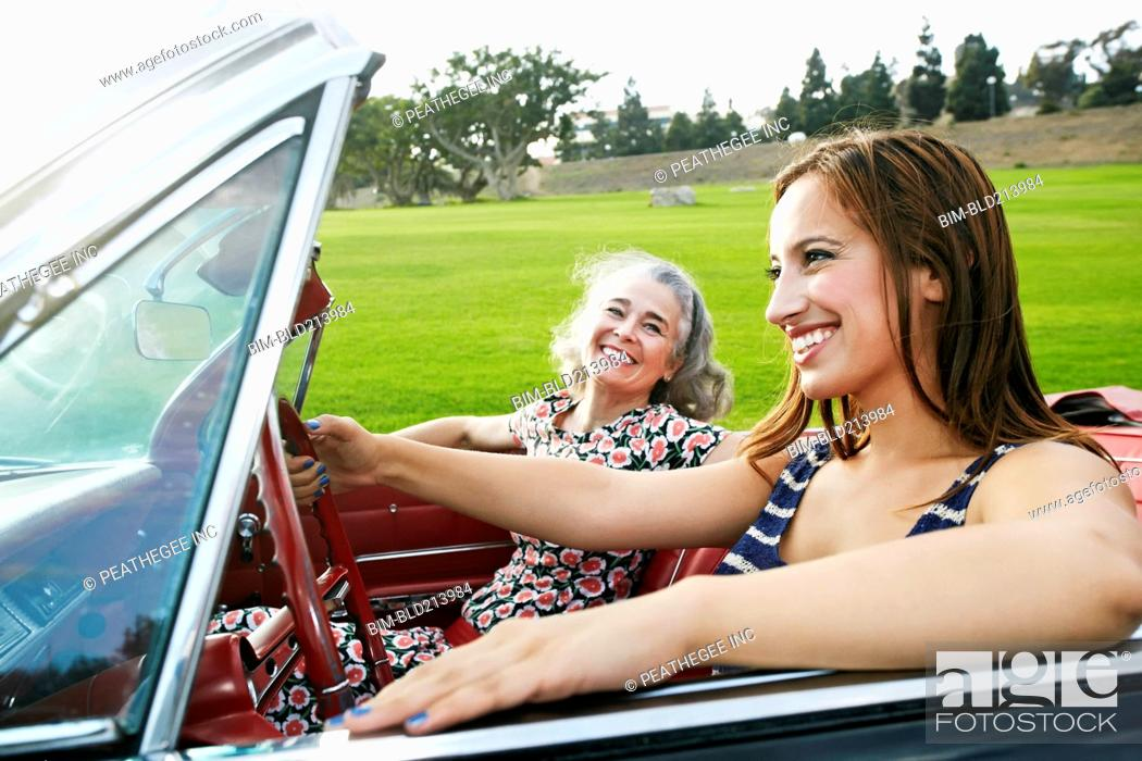 Stock Photo: Mother and daughter driving in classic convertible.