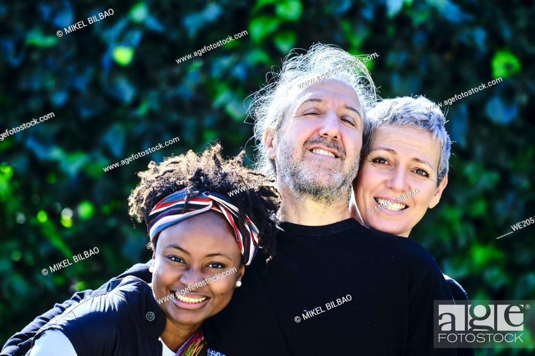 Imagen: Mature caucasian couple and a young african woman posing hugging outdoor in a family pose in a garden with a leaves background.