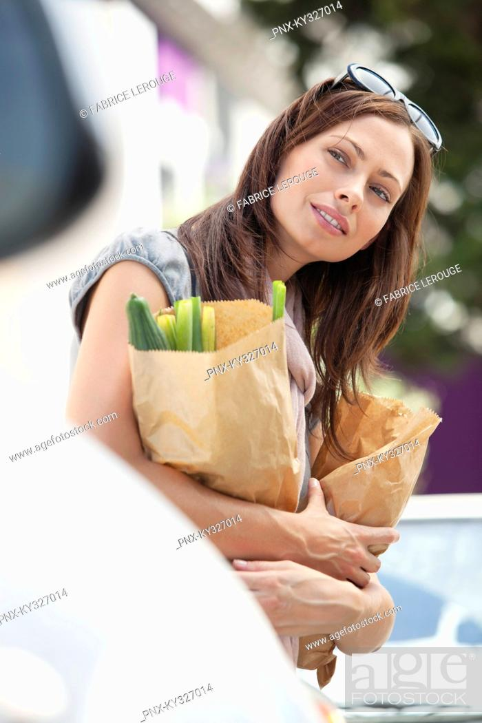 Stock Photo: Beautiful young woman looking away and holding paper bags full of vegetables.