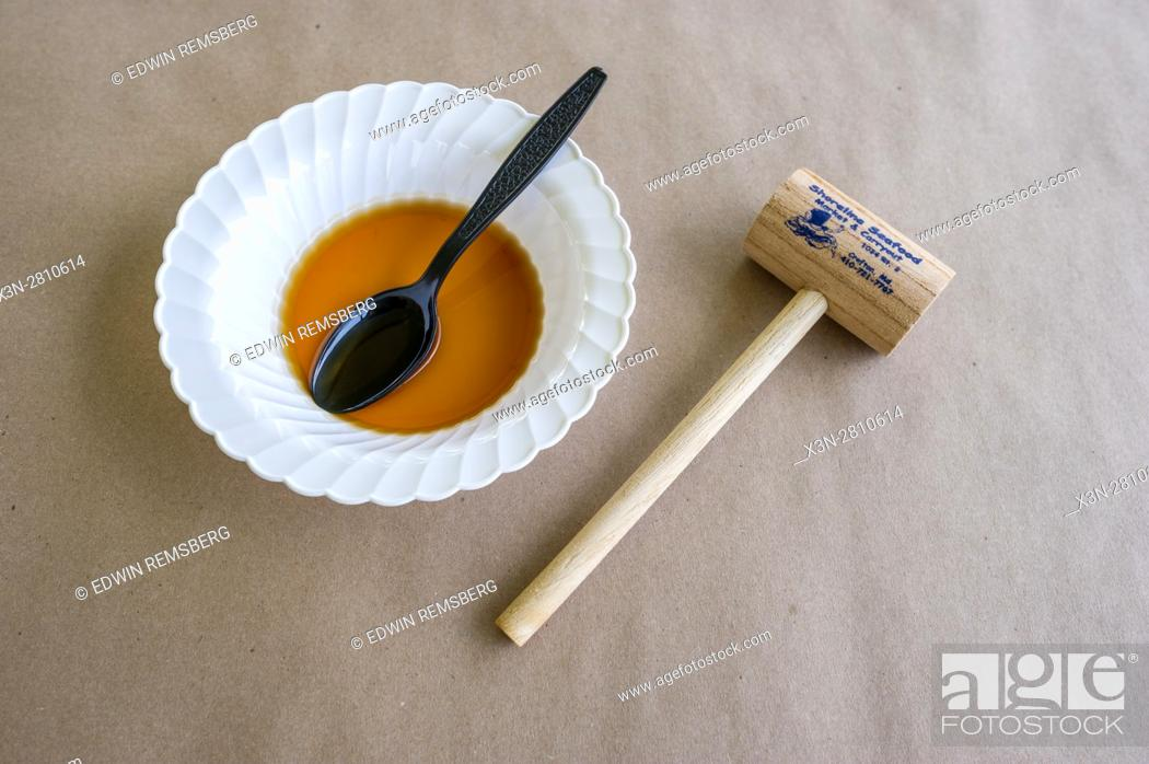 Photo de stock: A helping of crab soup next to a crab mallet on a picnic table.