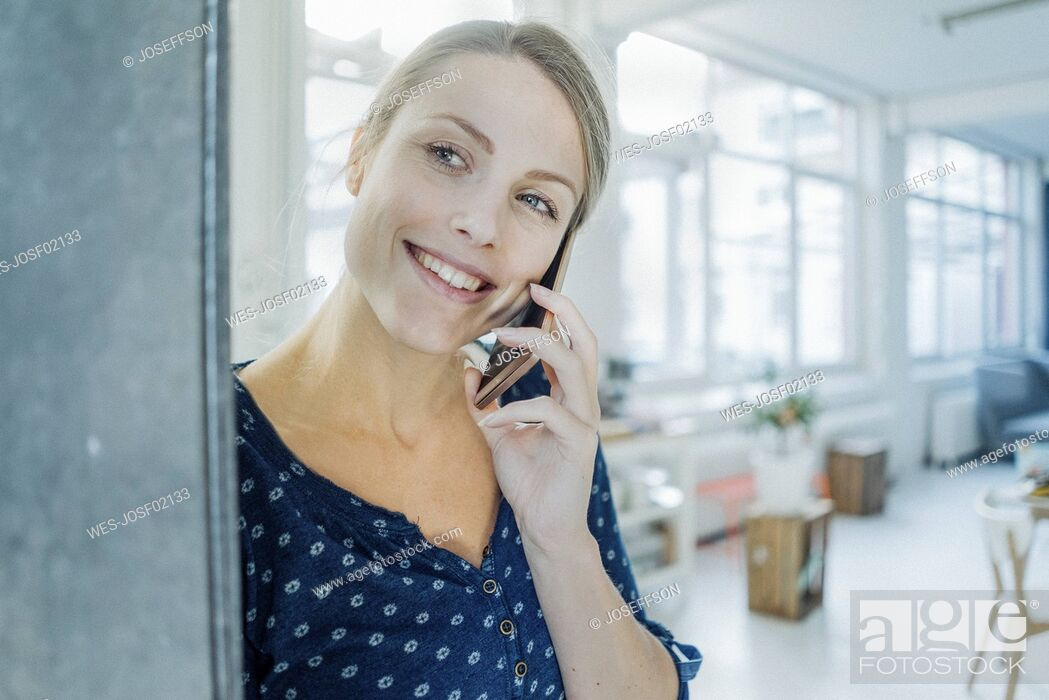 Stock Photo: Portrait of happy young woman on the phone in a loft.