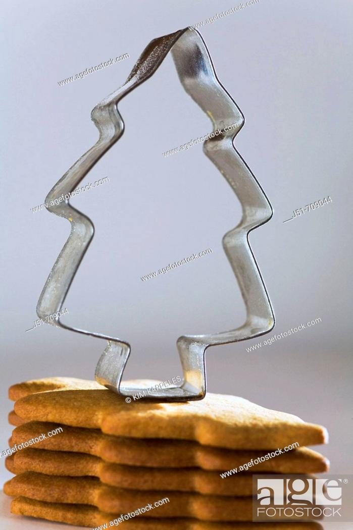 Stock Photo: Christmas stack of homemade gingerbread cookies cut in Christmas tree shape, metal cookie cutter.