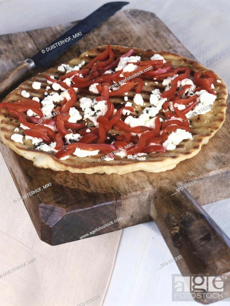 Stock Photo: Peppers and goat's cheese on pizza base.
