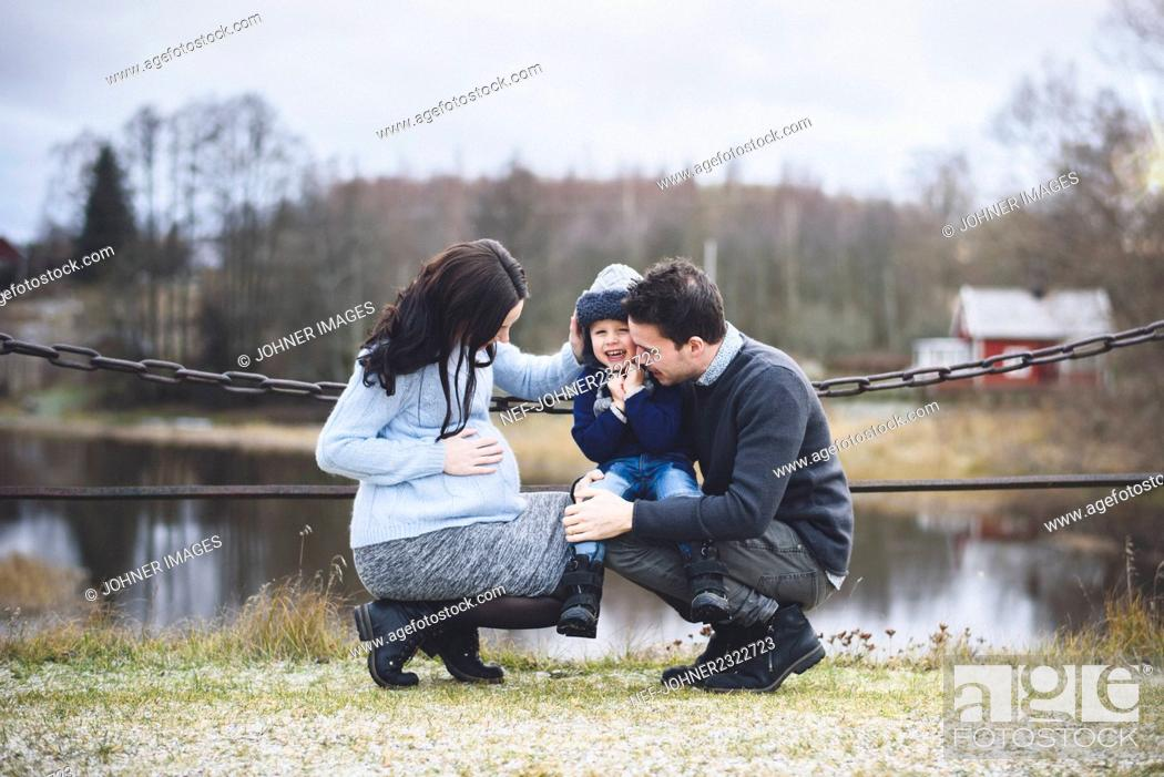 Stock Photo: Small boy with father and pregnant mother during walk.