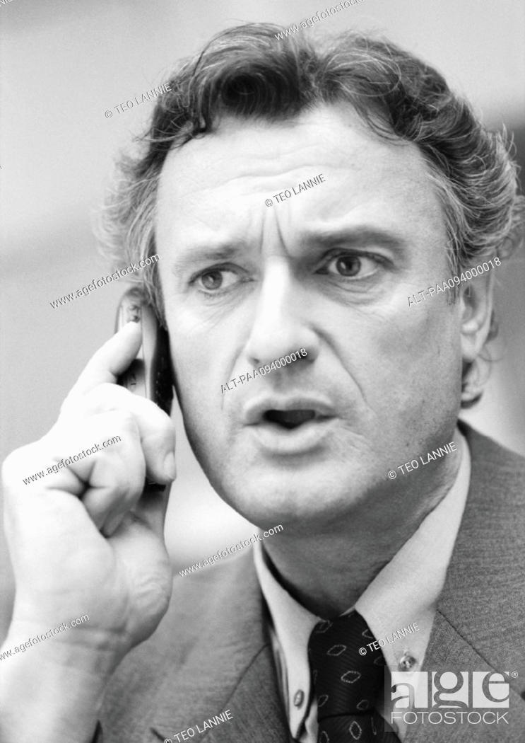 Stock Photo: Businessman using cell phone, close-up, B&W.