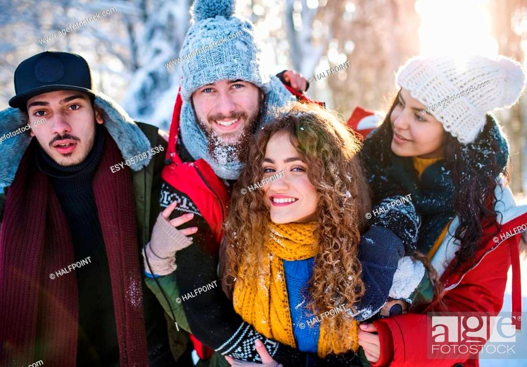 Stock Photo: A group of young cheerful friends on a walk outdoors in snow in winter forest, looking at camera.