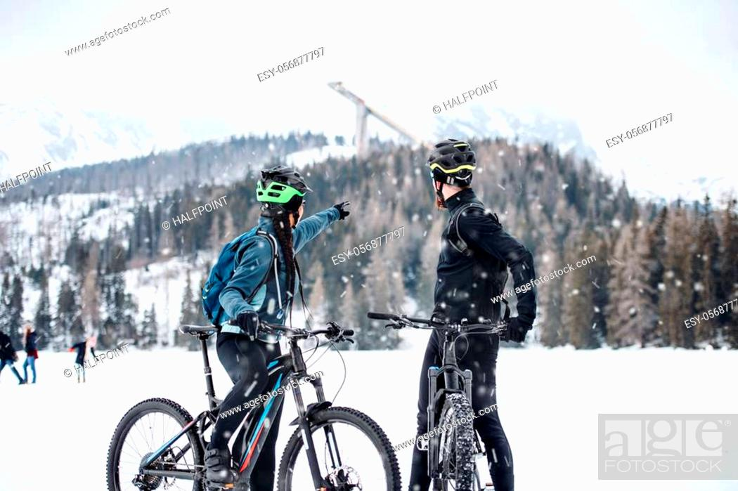 Stock Photo: Two mountain bikers resting outdoors in winter, talking.