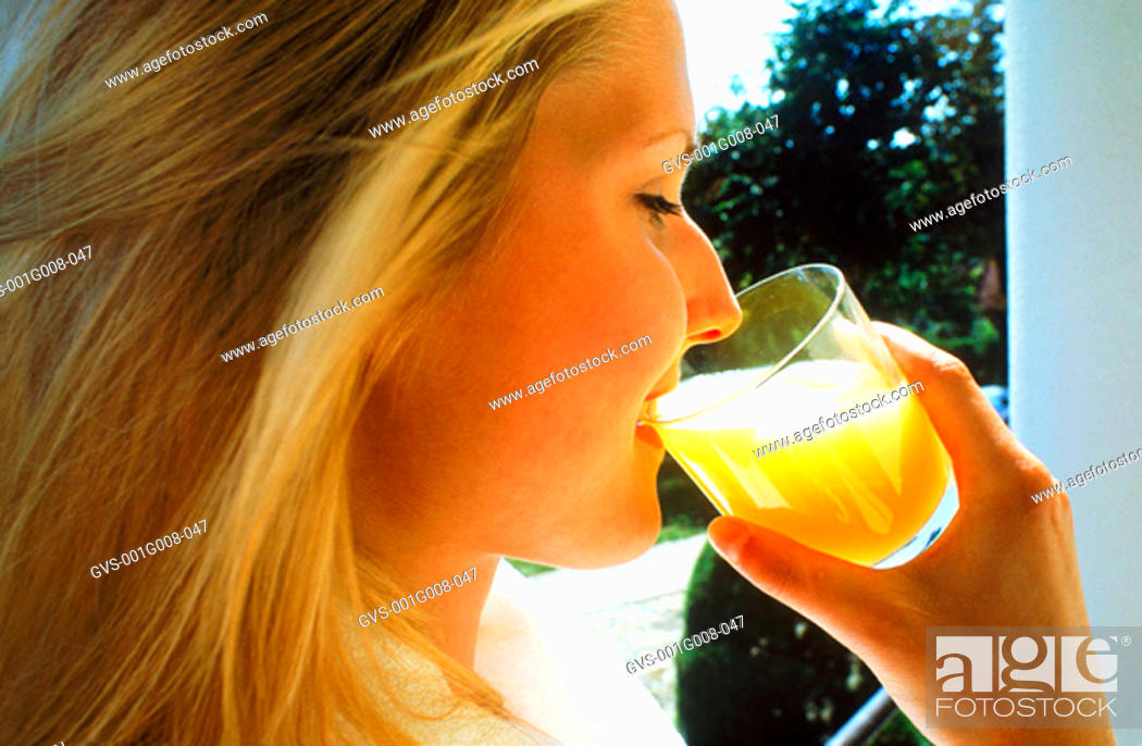 Stock Photo: Young woman drinking a glass of juice.