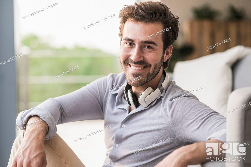 Imagen: Portrait of young man sitting in his livingroom.