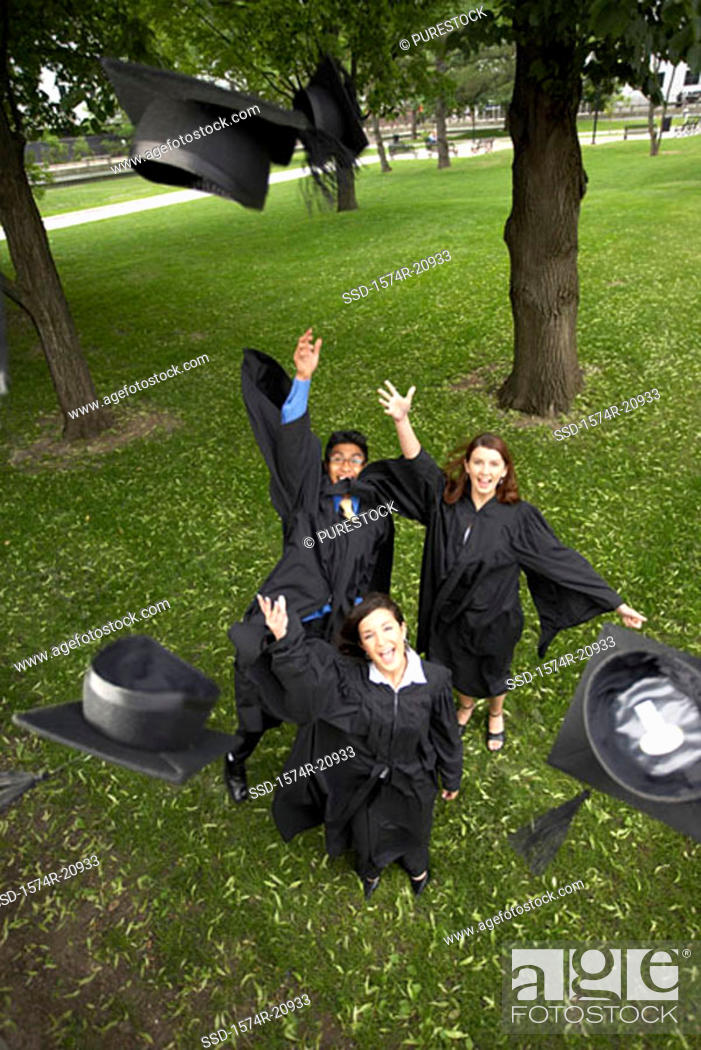 Stock Photo: Portrait of two female graduates and a male graduate throwing their mortarboards in the air.