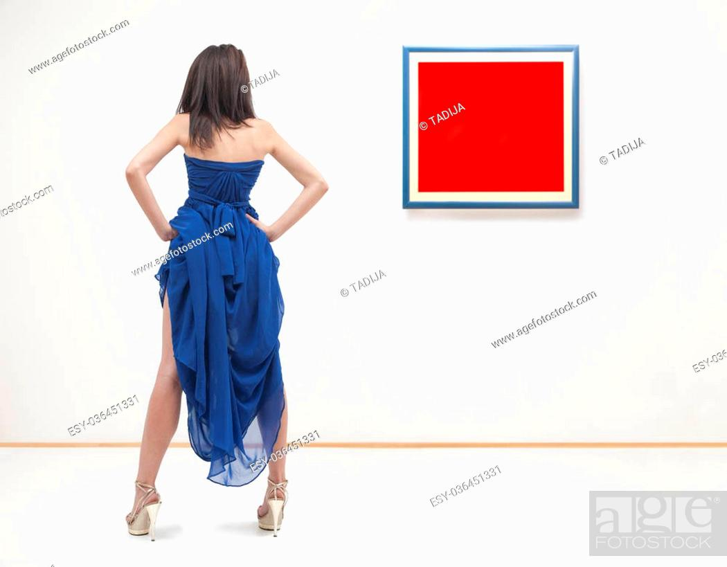 Imagen: Woman standing inside a gallery in front of two picture frames. Images are fill with red color useful for copy space.