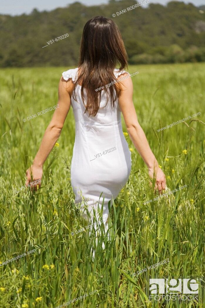 Stock Photo: Woman in white dress walking in the countryside.