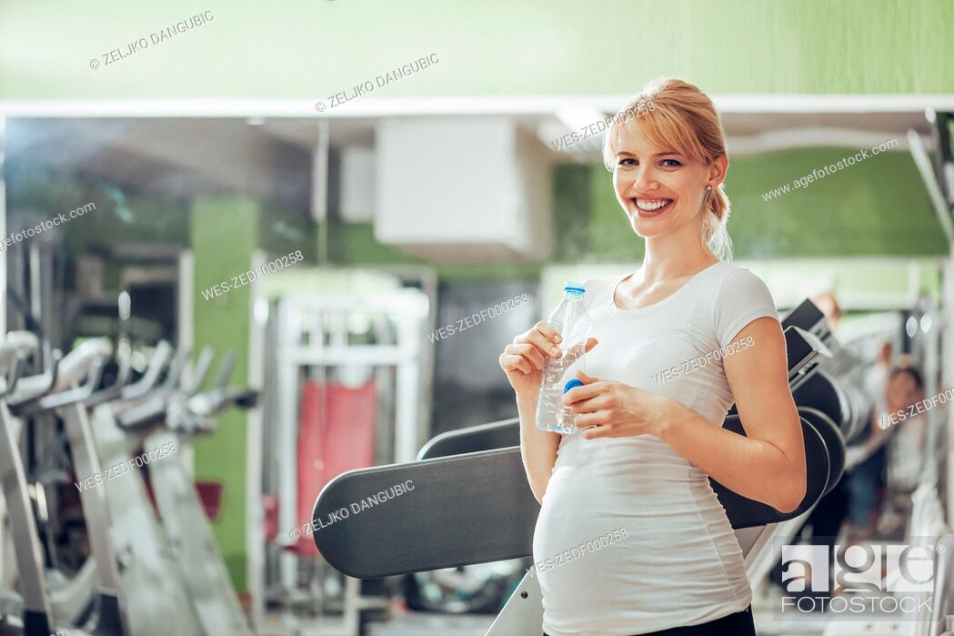 Photo de stock: Pregnant woman drinking water in gym.