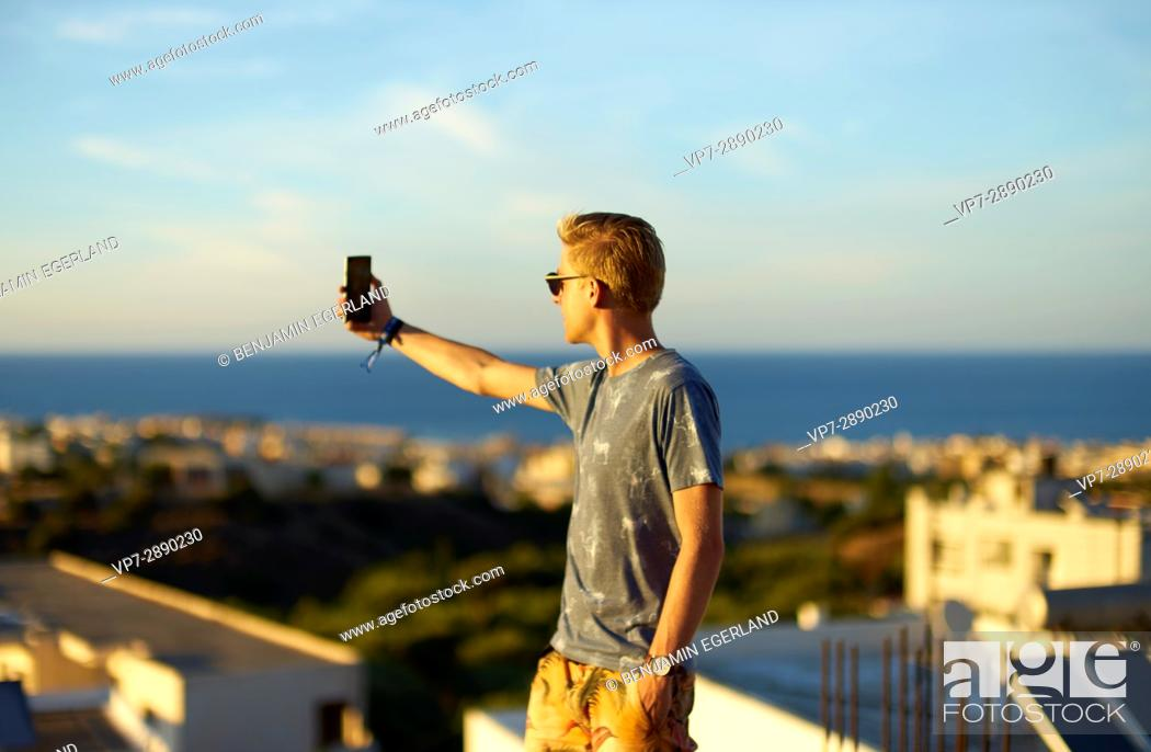 Stock Photo: young man taking selfie during sunset in holiday destination Hersonissos, Crete, Greece.