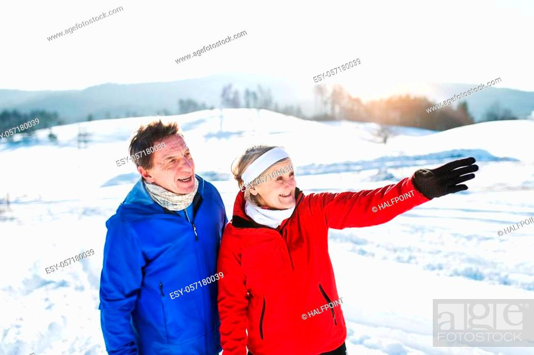 Stock Photo: Senior couple runners standing outside in winter nature, resting.
