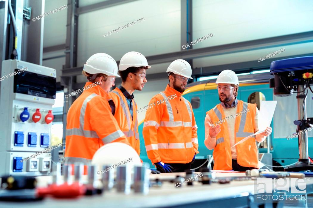 Stock Photo: Group of apprentices with instructor at railway engineering facility.