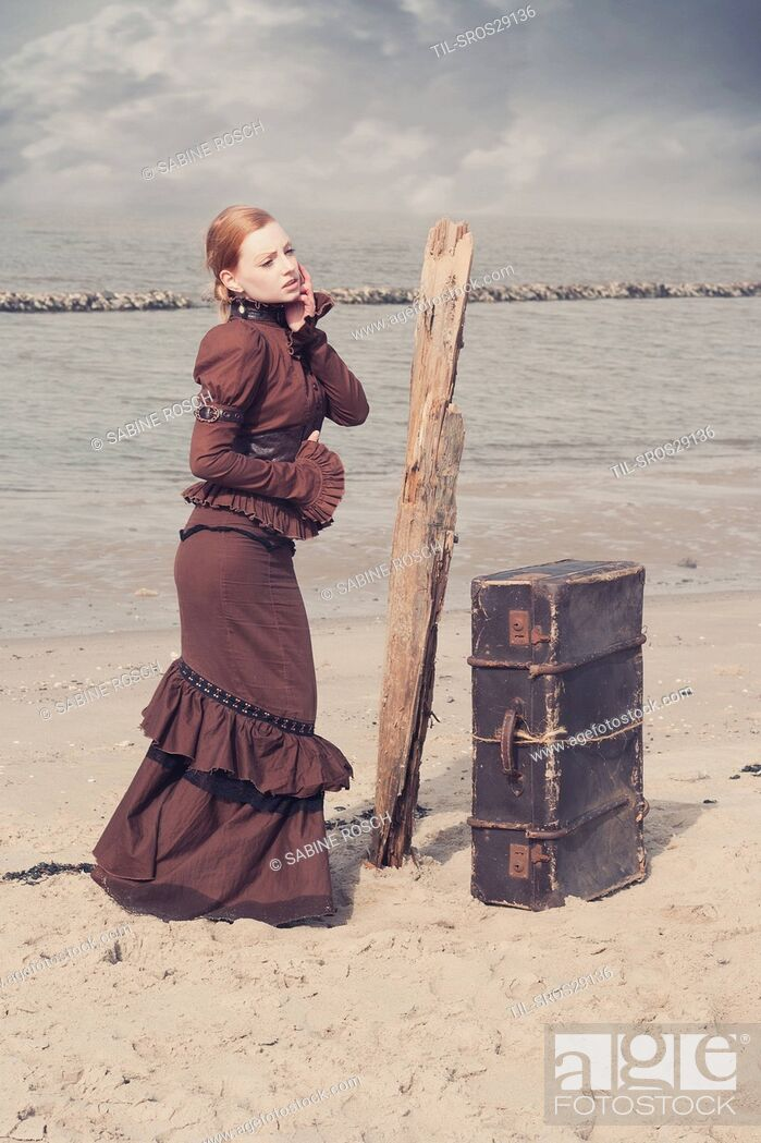 Imagen: Young woman in a victorian dress standing next to an old suitcase alone outdoors beside the sea.