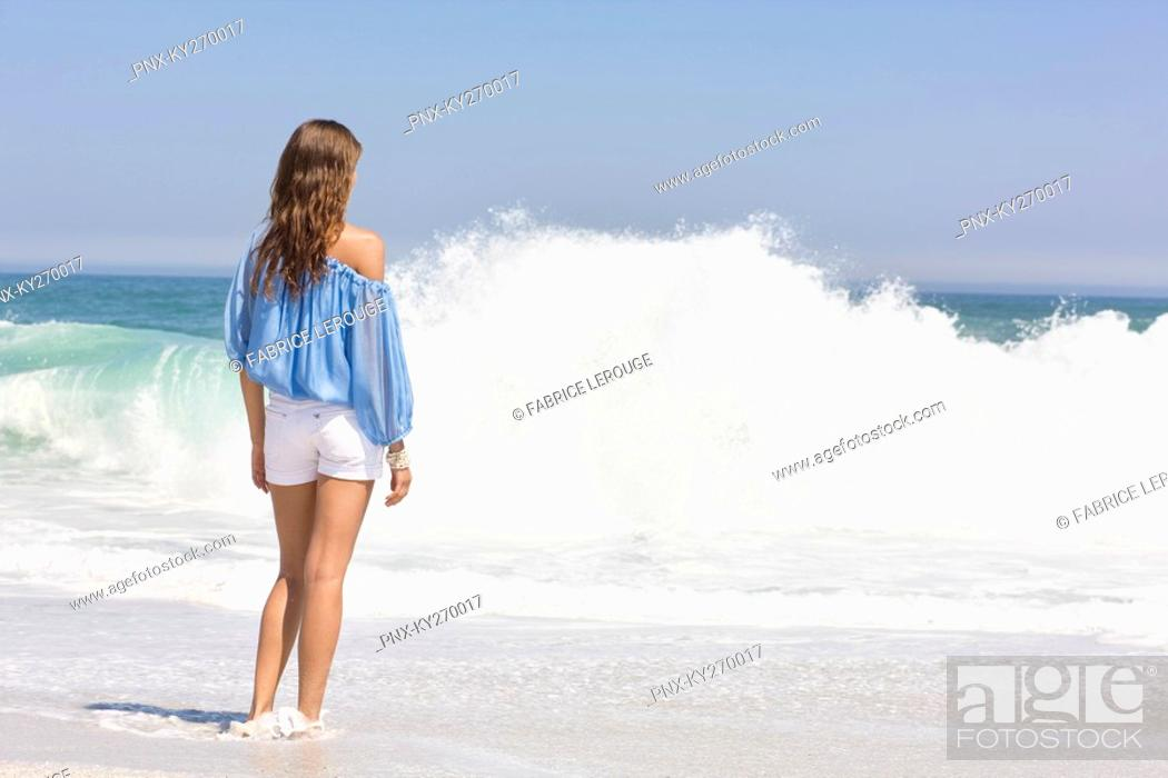 Stock Photo: Woman standing on the beach and looking at a view.