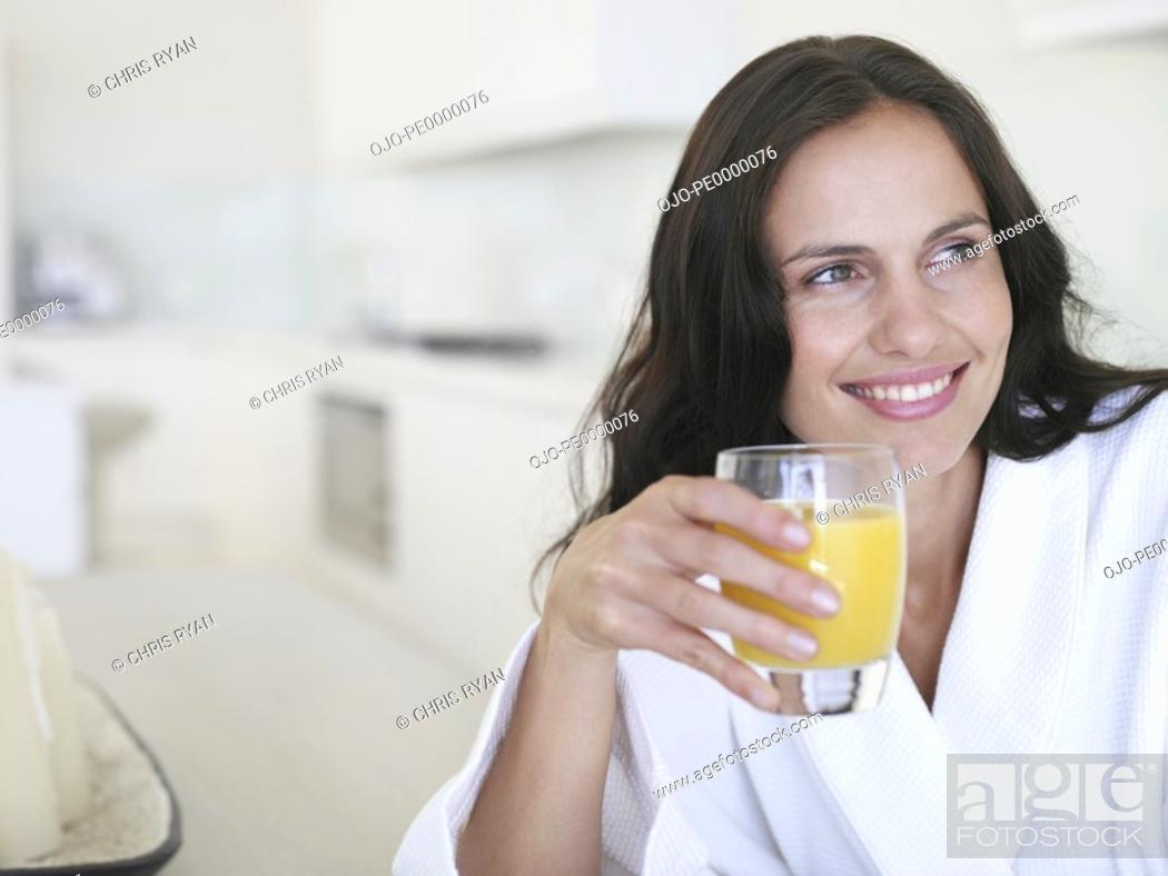 Stock Photo: Woman in robe with glass of orange juice smiling.