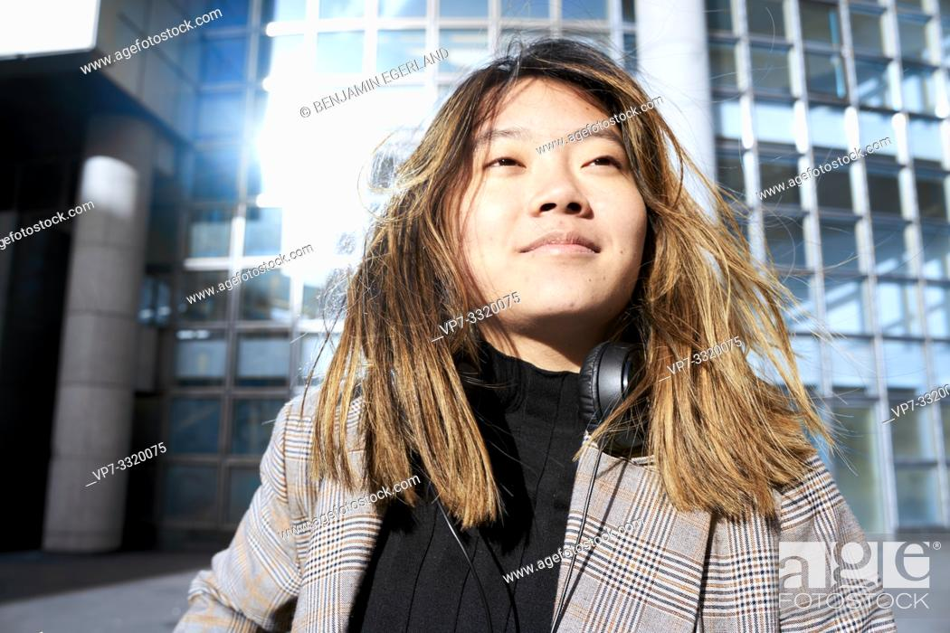 Stock Photo: young confident Asian woman in business district in Paris, France.