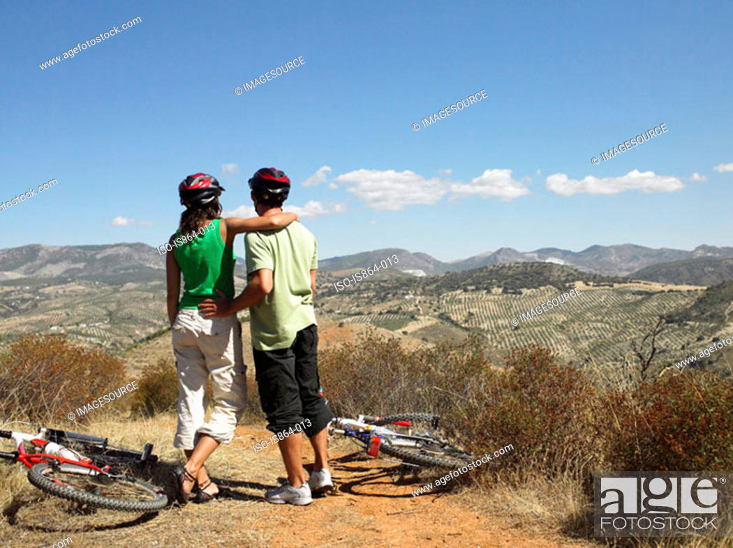 Stock Photo: Couple with bikes looking at view.