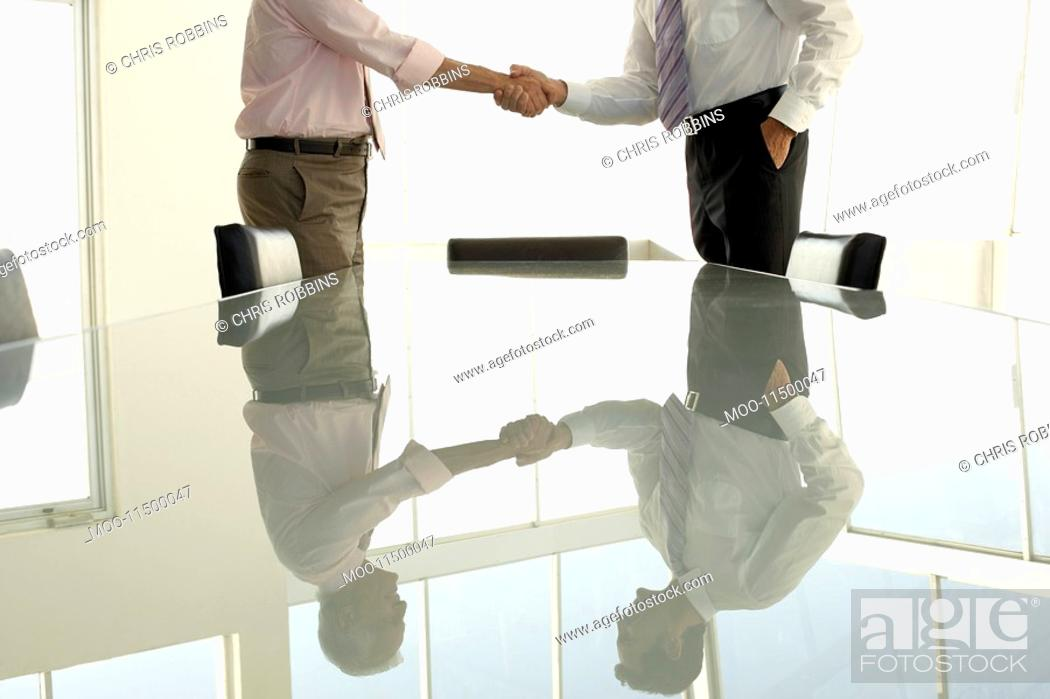 Stock Photo: Businessmen shaking hands by conference table mid section.