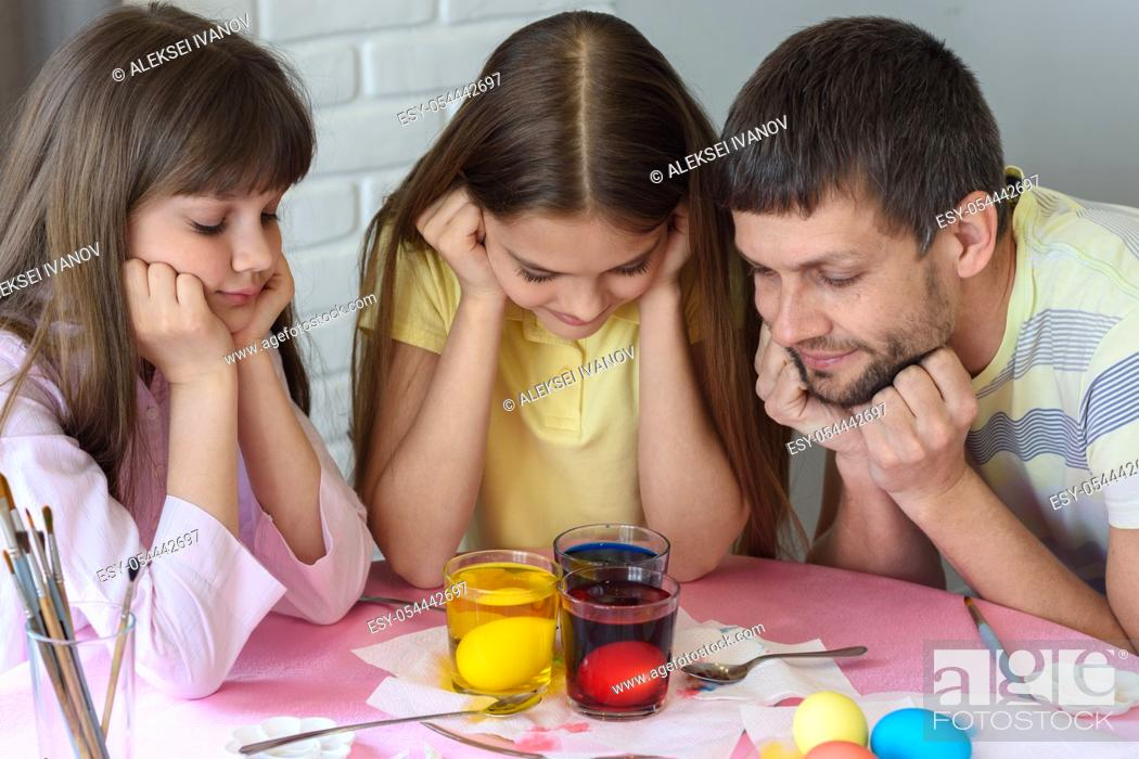 Stock Photo: Dad and two daughters are watching how the eggs are painted in glasses with dyes.