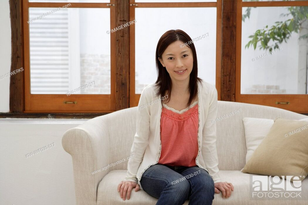Stock Photo: View of a cheerful young woman sitting on a sofa.