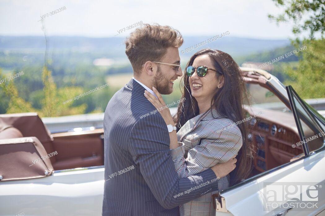 Photo de stock: Happy couple in front of luxury oldtimer car. Turkish ethnicity. Blogger Adem Bayalan. Bavaria, Germany.