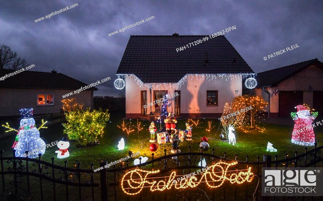 Stock Photo: Illuminated Christmas decoration light up the dark evening hours in the front garden of a family home in Pillgram, Germany, 5 December 2017.