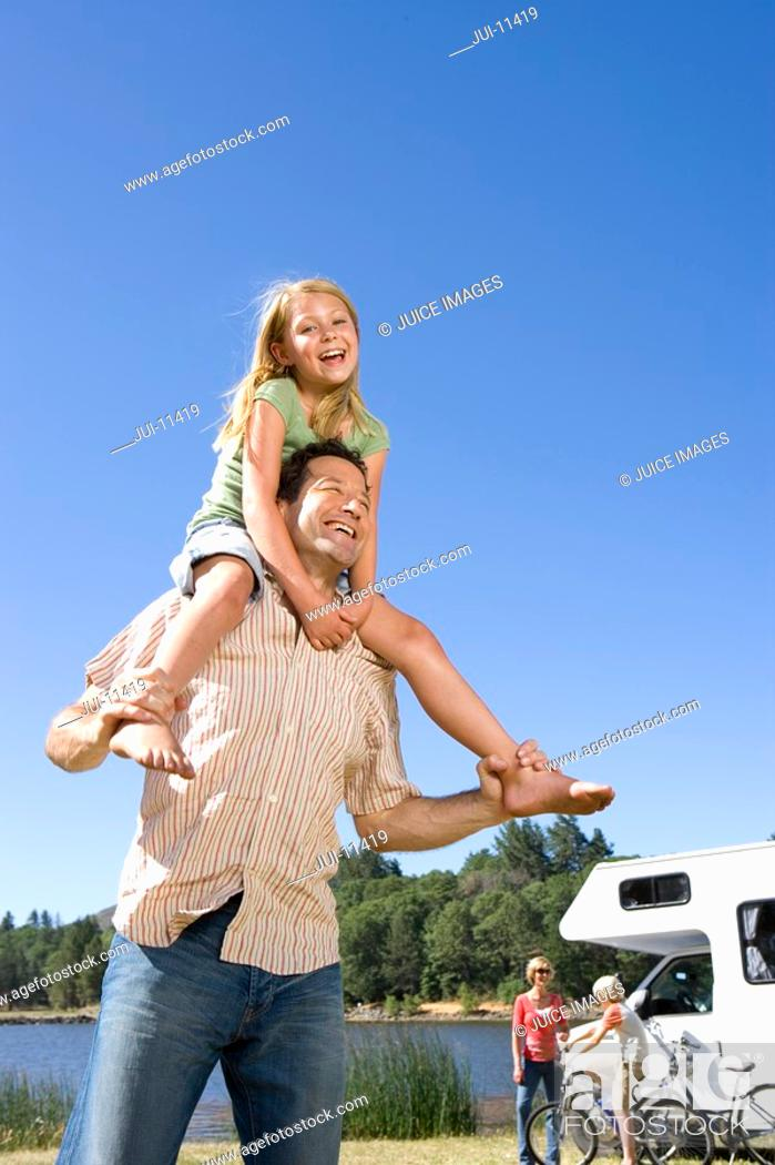 Stock Photo: Girl 9-11 on father's shoulders, mother and brother 10-12 by motor home in background, low angle view.