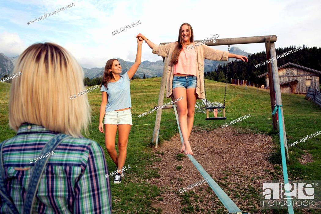 Stock Photo: Three female adult friends balancing on slackline in Austrian Alps, Sattelbergalm, Tirol, Austria.