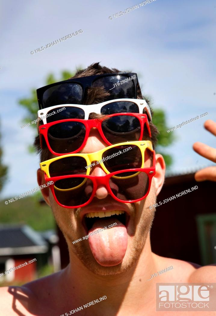 Stock Photo: Man with multiple sunglasses on, countryside of northern Sweden.
